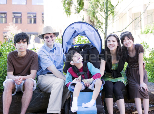 Father sitting with his biracial children and disabled son Stock photo © jarenwicklund