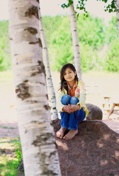 Young biracial girl sitting on rock under trees Stock photo © jarenwicklund
