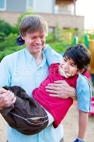 Caucasian father carrying biracial disabled son on playground Stock photo © jarenwicklund