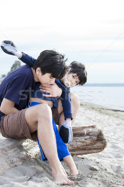 Big brother holding disabled boy on beach Stock photo © jarenwicklund