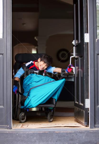 Handicapées garçon fauteuil roulant ouverture porte d'entrée souriant Photo stock © jarenwicklund