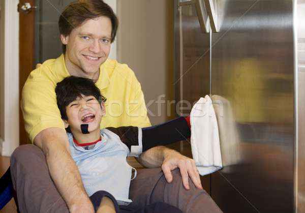 Father on kitchen floor with disabled son, cleaning the fridge Stock photo © jarenwicklund