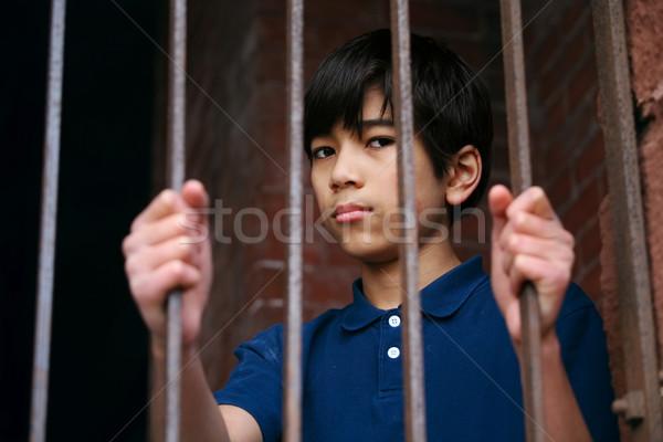 Boy standing behind bars Stock photo © jarenwicklund