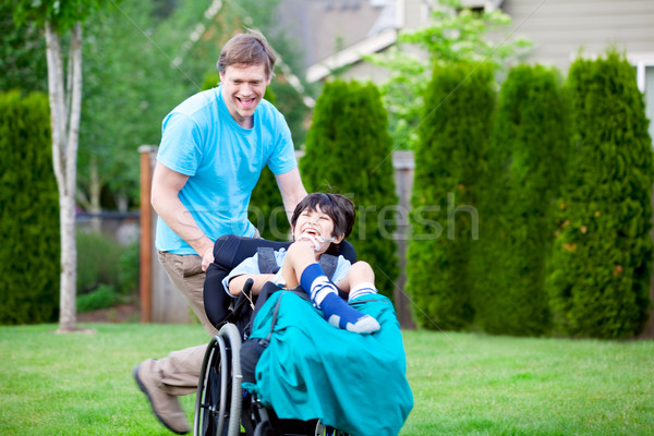 Father racing around park with disabled son in wheelchair Stock photo © jarenwicklund