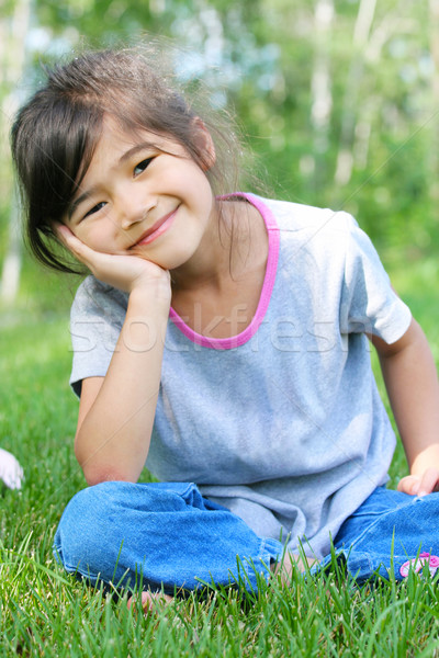 Child sitting on grass with a thoughtful expression. Stock photo © jarenwicklund