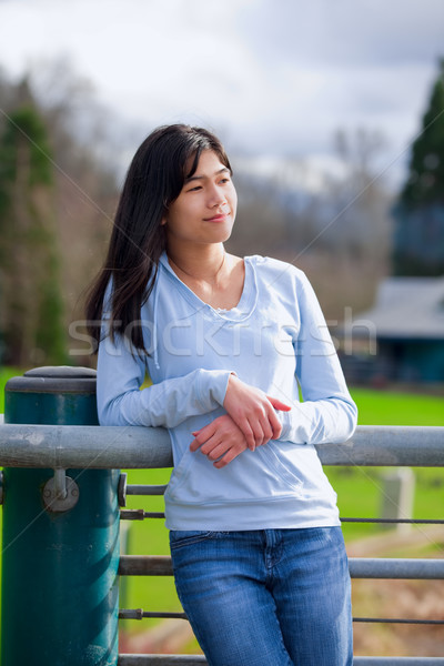 Young teen girl standing, leaning against railing at park Stock photo © jarenwicklund