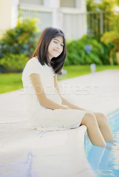 Ten year old girl repaxing by swimming pool, smiling Stock photo © jarenwicklund