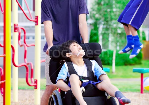 Disabled boy in wheelchair enjoying watching friends play at par Stock photo © jarenwicklund