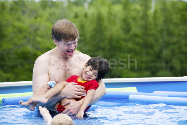 Stock photo: Father holding disabled son in pool