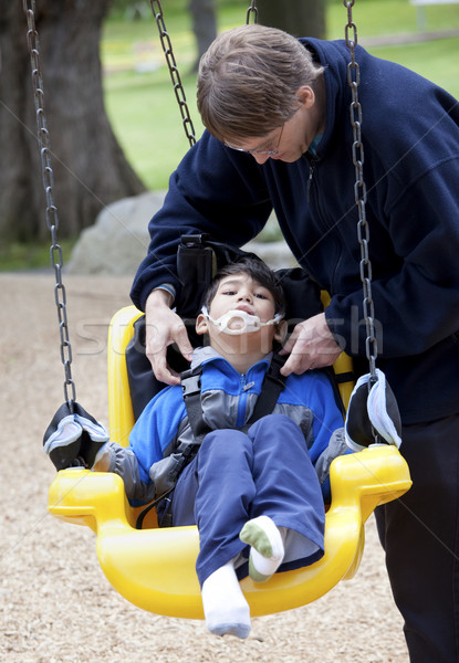 Father pushing disabled son  on handicap swing Stock photo © jarenwicklund