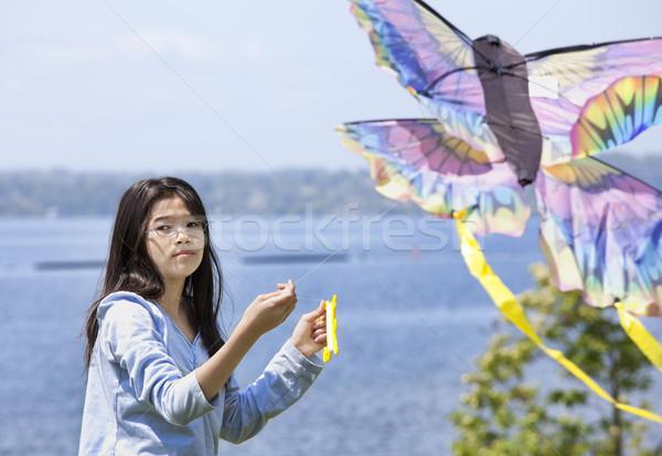 Biracial asian girl flying kite by the lake Stock photo © jarenwicklund