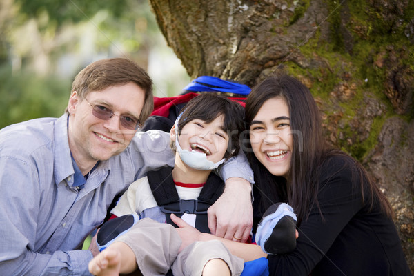 Disabled boy in wheelcahir surrounded by father and sister Stock photo © jarenwicklund