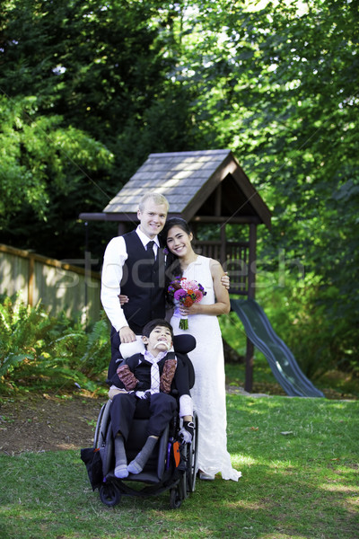 Interracial bride and groom standing with her disabled little bo Stock photo © jarenwicklund