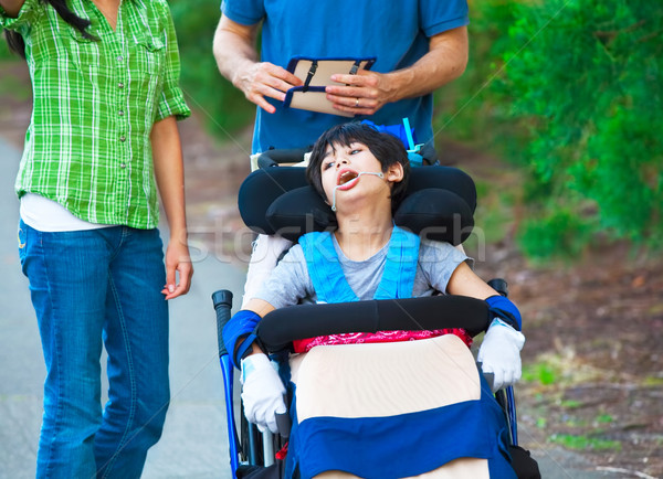 Disabled child in wheelchair outdoors with caregivers or family Stock photo © jarenwicklund