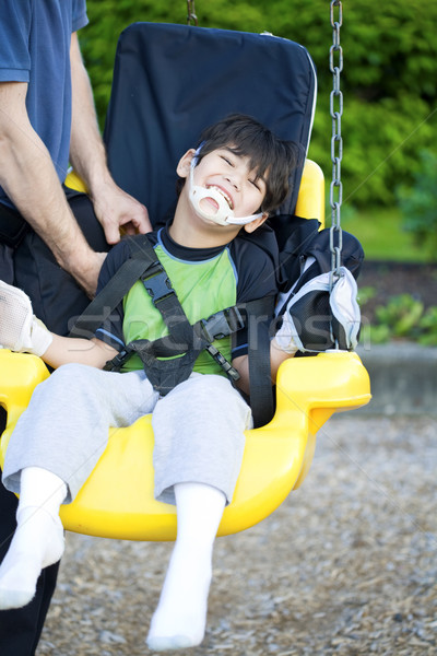 Disabled five year old boy in handicap swing Stock photo © jarenwicklund