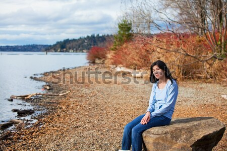 Young teen girl in blue shirt and jeans sitting along rocky lake Stock photo © jarenwicklund