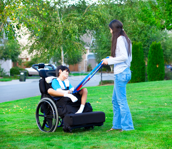 Biracial older sister playing outdoors with disabled little brot Stock photo © jarenwicklund