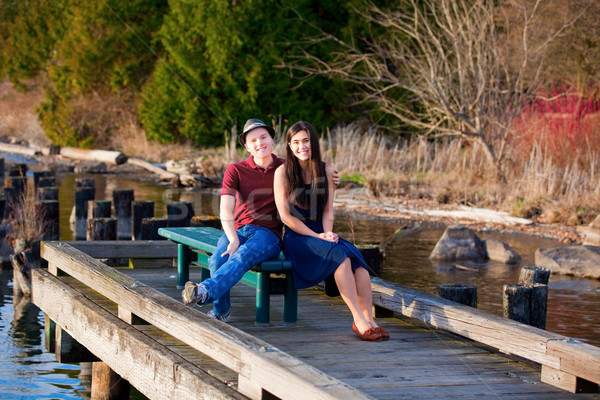 Young interracial couple sitting together on dock over lake Stock photo © jarenwicklund