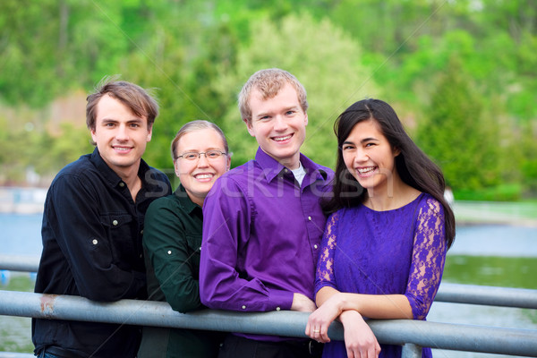 Four young multiethnic friends together outdoors by lake Stock photo © jarenwicklund