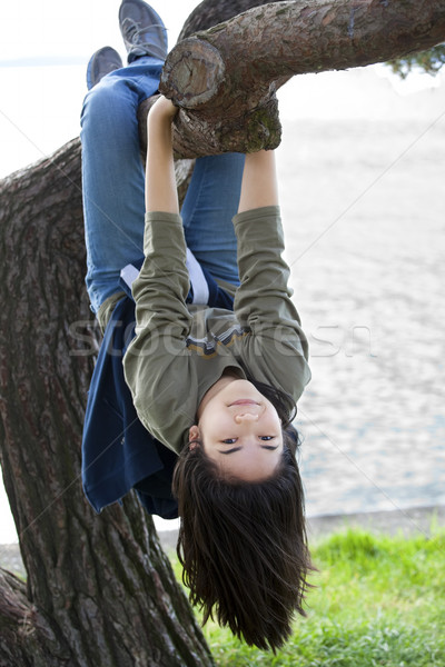 Young teen girl hanging upside down on tree limb Stock photo © jarenwicklund