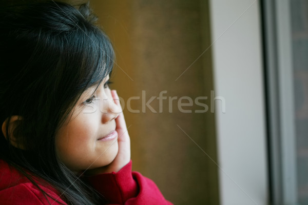 Little Asian girl quietly sitting by window, hand on chin Stock photo © jarenwicklund