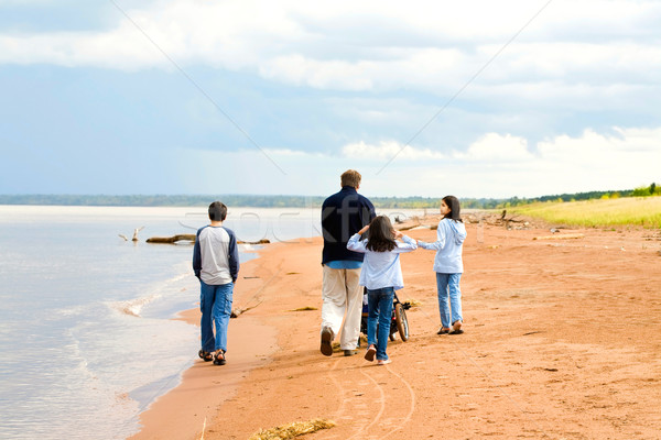 Father and children strolling along the deserted lake shore on s Stock photo © jarenwicklund