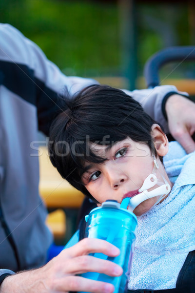 Disabled biracial little boy in wheelchair drinking water from s Stock photo © jarenwicklund