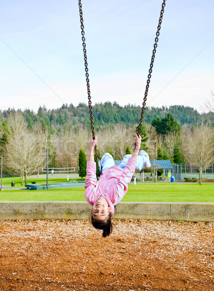 Happy little nine year old part Asian girl on the swings at park Stock photo © jarenwicklund