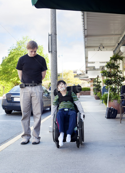 Father walking next to disabled son in wheelchair through town Stock photo © jarenwicklund