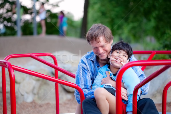 Father holding disabled son on merry go round at playground Stock photo © jarenwicklund