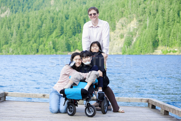 Disabled boy in wheelchair surrounded by family on lake pier Stock photo © jarenwicklund