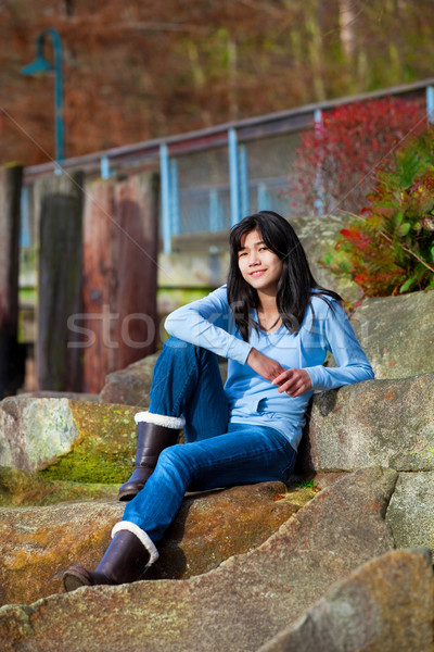Stock photo: Young teen girl relaxing on large boulder along lake shore, smil