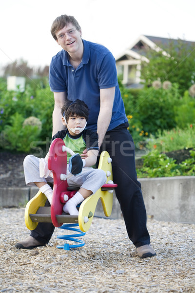 Stock photo: Father helping disabled son play at playground