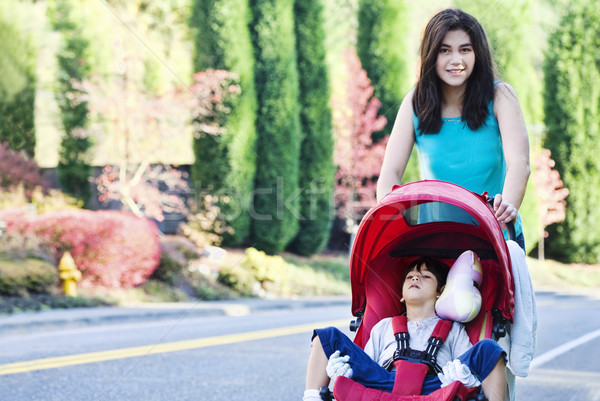 Teen girl pushing her little brother in stroller Stock photo © jarenwicklund