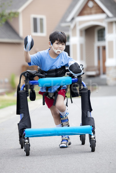 Stock photo: Six year old disabled boy walking in walker down the street
