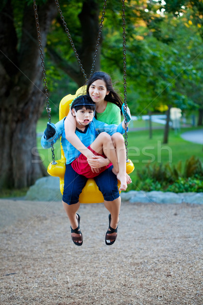 Big sister holding disabled brother on special needs swing at pl Stock photo © jarenwicklund
