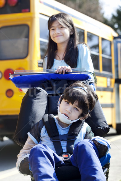 Big sister pushing disabled brother in wheelchair at school Stock photo © jarenwicklund