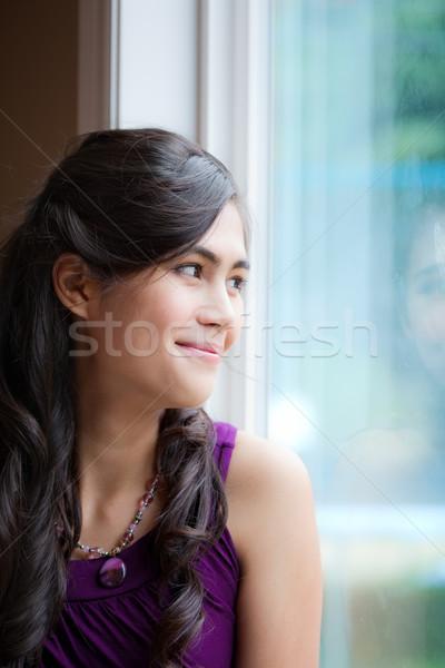 Beautiful biracial young woman smiling by window Stock photo © jarenwicklund