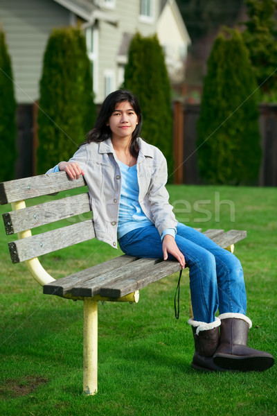 Young biracial teen girl relaxing outdoors on park bench Stock photo © jarenwicklund
