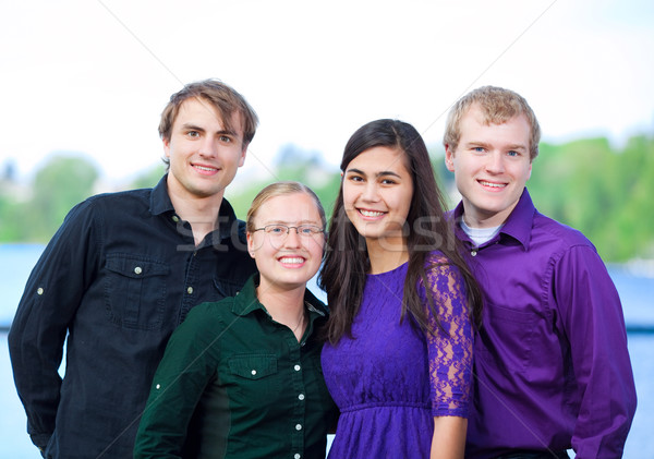 Four young multiethnic friends standing  together outdoors Stock photo © jarenwicklund