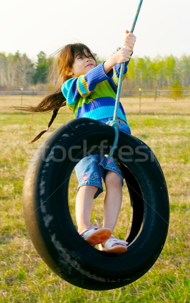 Little girl swinging on tire swing in the countryside Stock photo © jarenwicklund