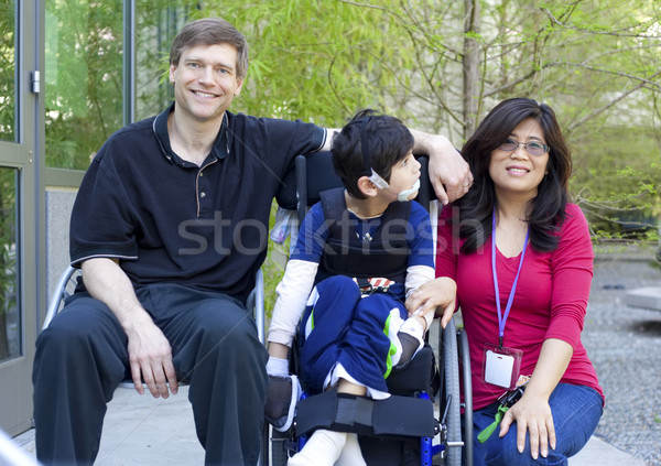 Disabled child in wheelchair with his parents Stock photo © jarenwicklund