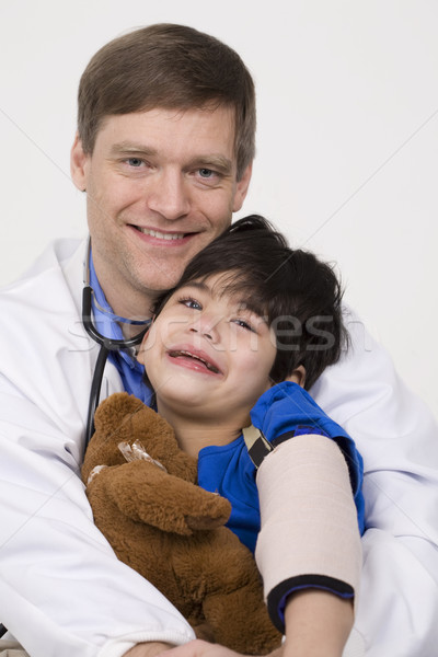 Male doctor comforting disabled  toddler patient on lap Stock photo © jarenwicklund