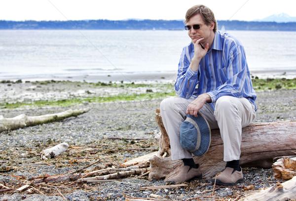Depressed man sitting on driftwood on beach Stock photo © jarenwicklund