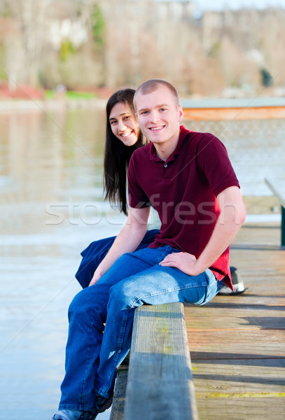 Beautiful interracial couple sitting on wooden dock over lake Stock photo © jarenwicklund