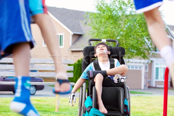 Disabled child in wheelchair watching children play at park Stock photo © jarenwicklund