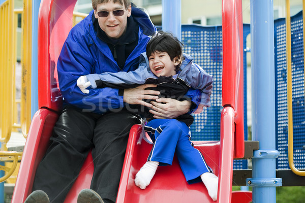 Father going down slide with disabled son who has cerebral palsy Stock photo © jarenwicklund