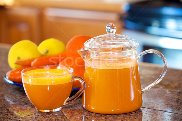 One cup of orange colored juice on kitchen counter with fruit an Stock photo © jarenwicklund