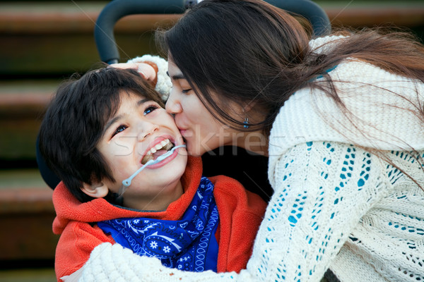 Big sister kissing disabled little brother seated in wheelchair  Stock photo © jarenwicklund