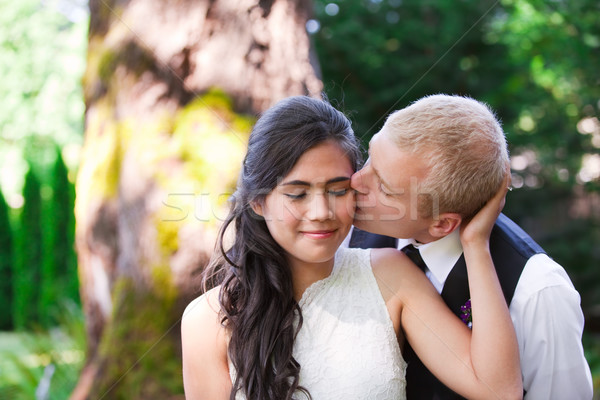 Caucasian groom lovingly kissing his biracial bride on cheek. Di Stock photo © jarenwicklund